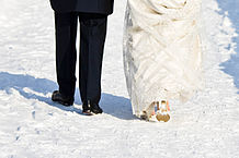 View of bride and groom walking on snow--Legs only