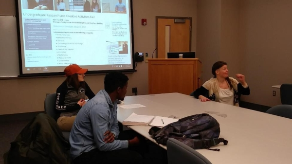 A professor and students discuss poster design.