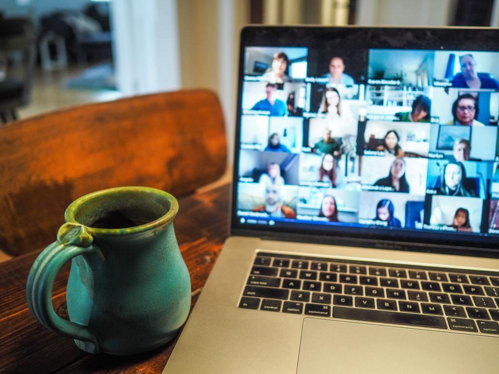 coffee mug beside Macbook running a Zoom meeting