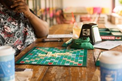 A person thinking in front of a Scrabble board